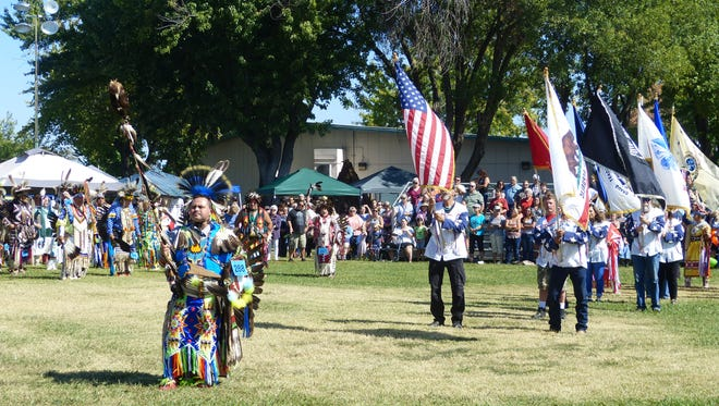 Dancers and spectators hold a moment of silence for prayer following a collective dance at  Redding Rancheria's Stillwater Pow Wow on Saturday at the Shasta District Fair grounds in Anderson.
