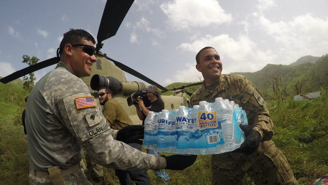 CH-47 Chinook helicopter mechanics from the 2nd Battalion, 501st Aviation Regiment --- Spc. Jose Olan, left, from Mayaguez, Puerto Rico, and Pfc. Angel Vega from Sabana Grande, Puerto Rico -- unload water from FEMA to the residents of Coamo.