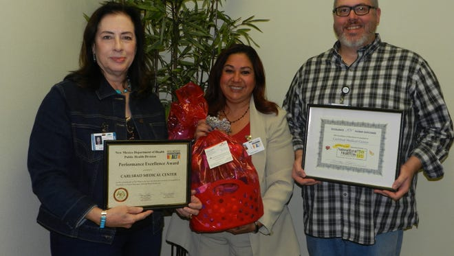 Carlsbad Medical Center CEO Cathy Hibbs (left) and Chief Nursing Officer Sam Jones accept an award from New Mexico Department of Health representative Anita Lovato.