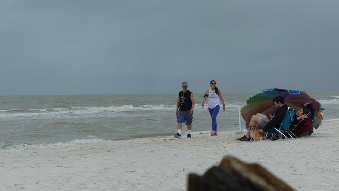 Vanderbilt Beach in North Naples drew people Saturday, Dec. 9, 2017, despite the cloudy, cooler weather. A cold front was forecast to bring near-record lows to Southwest Florida. Temperatures could dip into the low 40s by Sunday morning, Dec. 10.