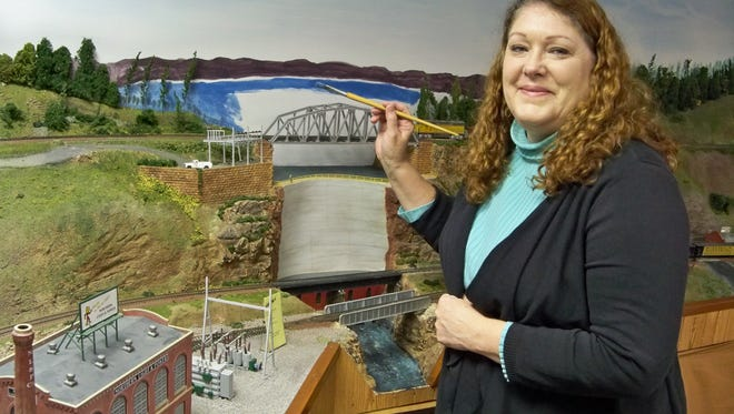 The Clipper City Model Railroad Club, located on the Manitowoc County Expo grounds, will host its Christmas Train Show Dec. 29-30. Shown working on the layout is artist Paula Hammond.