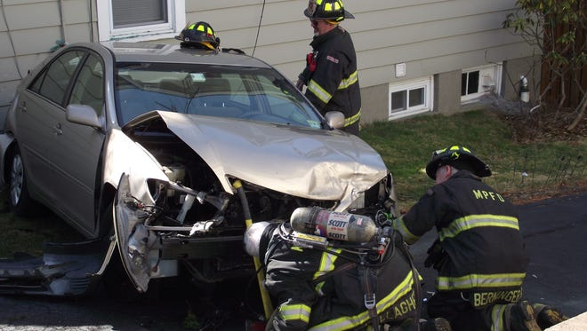 Firefighters attended to a car that hit a house following a three-car accident at Vreeland and Franklin avenues.