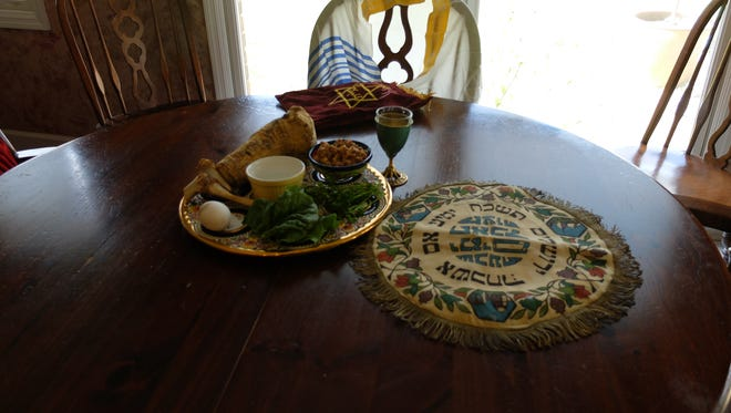 Preparations for a Passover Seder include a Seder plate, three pieces of matzot in a cover and a cup set for the prophet Elijah.