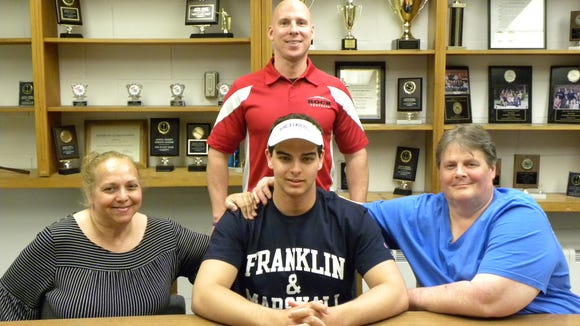 Glen Rock High School senior Jimmy Gilmartin is joined by his mother Virginia and father James in celebration of his commitment to play football at Franklin & Marshall College in Lancaster, Pa.  Also on hand to congratulate Jimmy is GRHS Head Football Coach Jim Kurz (standing.) Jimmy was a two-year starter on both the offensive and defensive lines for the Panthers. He was named 1st Team All-League Selection and served as senior captain this year.