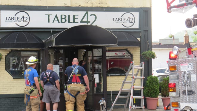 Fire fighters inspect an awning that caught fire in the early morning hours of June 19, 2018, at Table 42 restaurant on N. Sussex Street in Dover, across from Town Hall.