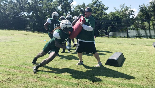 Linebacker Jibreel Hazly works on using his forearm to fight through blocks with his position coach, Ryan Smith.