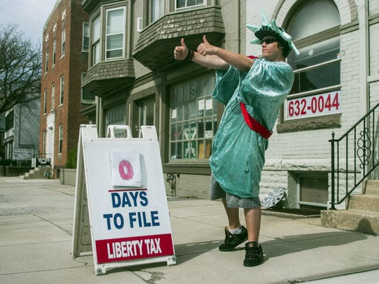 Klay Kinna, a mascot with Liberty Tax, gestures at passing traffic on Frederick Street in downtown Hanover in front of Liberty Tax offices April 15.