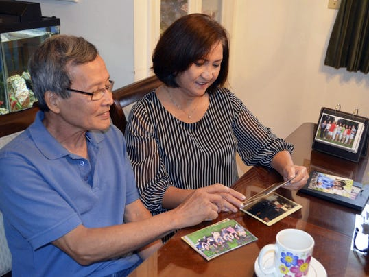 Dung and Loi Phung sit in their Cleona living room, looking back at photos from their last 40 years in America.