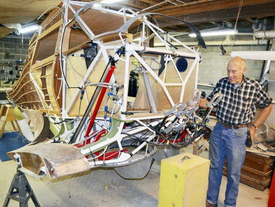 "Saying it's like building a model plane only bigger, Warren ""Doc"" Daugherty explains the configuration of the rudder pedals he fabricated for the Staggerwing plane under construction. The pedals are just a few of the 10,000 parts that are going into the plane."