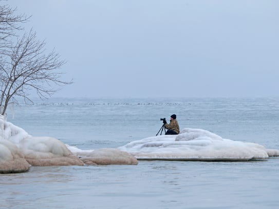 """I'm trying to get the photo nobody else has,"" Tim Holte of Milwaukee said as he perched himself Wednesday on a mound of ice near Bradford Beach in Milwaukee while taking photos of the Lake Michigan shoreline that's covered in ice."