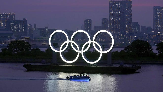 The Olympic rings float in the water Wednesday at sunset in the Odaiba section in Tokyo. The Japanese public is being prepared for the reality of next year's postponed Olympics where athletes are likely to face quarantines, spectators will be fewer, and the delay will cost taxpayers billions of dollars. In the last several weeks, IOC President Thomas Bach has given selected interviews outside Japan and hinted at empty stadiums, quarantines and virus testing.
