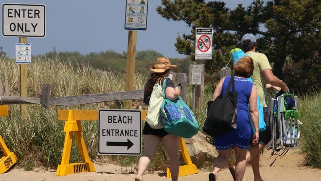 Beachgoers adhere to the new one-way signs at Crosby Landing Beach in Brewster, designed to keep interactions limited.