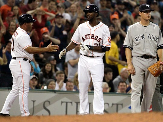 Houston Astros's Dexter Fowler (21) is congratulated by third base coach Pat Listach, left, after hitting a triple in the third inning of an MLB American League baseball game against the New York Yankees, Wednesday, April 2, 2014, in Houston. (AP Photo/Patric Schneider)