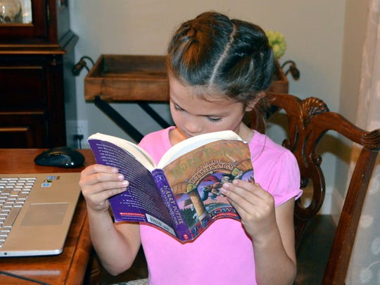 "In this Nov. 2, 2017 photo, Mary Laine Dyksterhouse, 8, who writes online book reviews under the name Emmie Enchanted, reads one of her favorite books, ""Harry Potter And The Sorcerer's Stone,"" at her home in Greenwood, Miss."