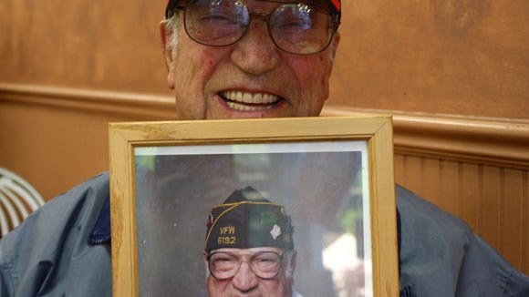 Westwood High School fan Vito Trause holds up a picture from the VFW post of himself.