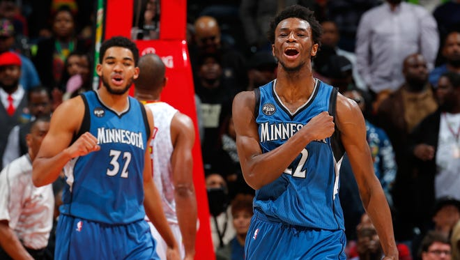 Andrew Wiggins, right, of the Minnesota Timberwolves reacts after drawing a foul on a basket against the Atlanta Hawks at Philips Arena on November 9, 2015 in Atlanta, Georgia.