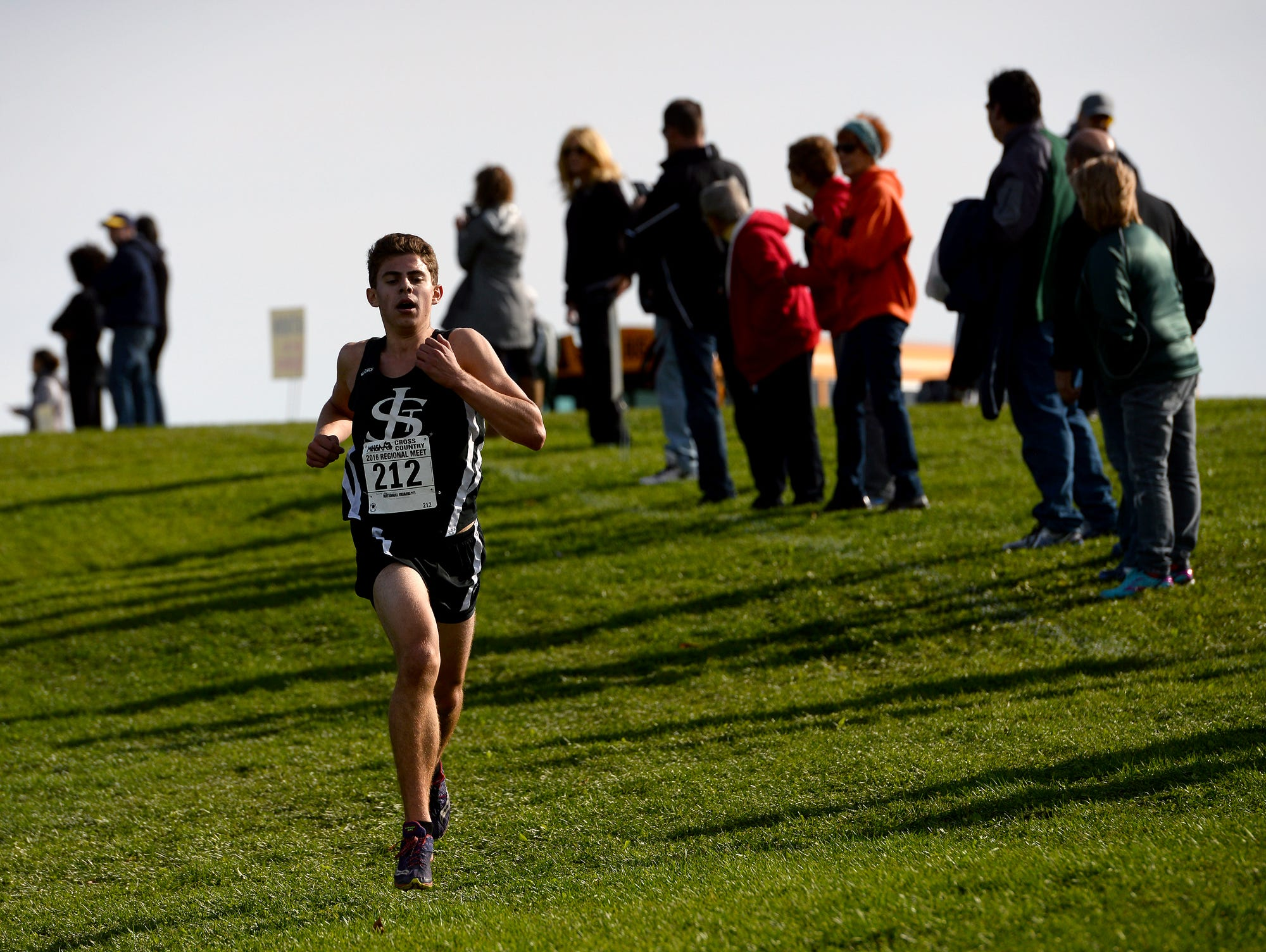 St. Johns' Dillan Haviland leads the pack down the hill in the Division 2 regional cross country meet at Uncle John's Cider Mill Friday, October 28, 2016, in St. Johns.