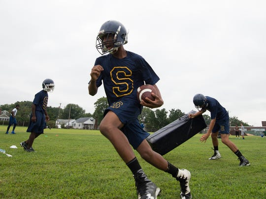 Seaford's Sihon Evans runs with the ball past a blocker during the first day of high school football practice.