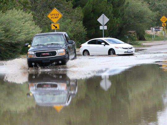 A truck makes it way over standing water on Love Road on Thursday in El Paso's Upper Valley. Overnight rains left areas of West El Paso and Canutillo flooded.