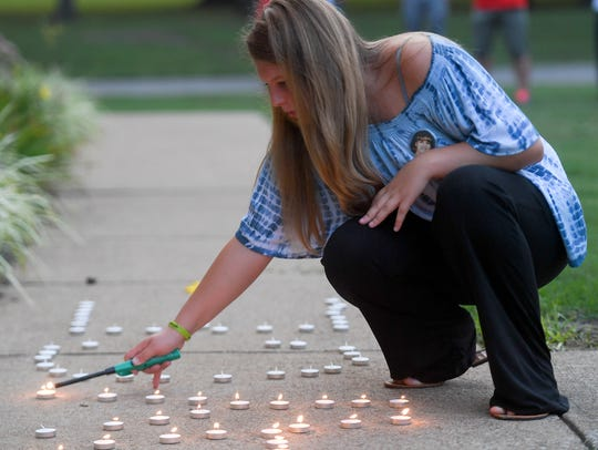 McKenzie Gross lights candles that spell out Cayce