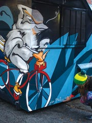 Morrisville artist Jess Graham works on a mural in
