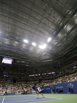 Under the closed roof at Arthur Ashe Stadium, Andreas Seppi returns a shot to Rafael Nadal.