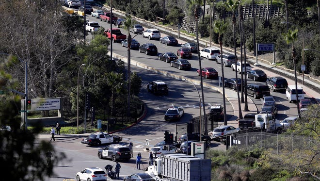 Traffic backs up as emergency vehicles arrive at the Naval Medical Center San Diego, Tuesday, Jan. 26, 2016, in San Diego. The Navy said authorities responded to a report of gunshots at a building on the campus. (AP Photo/Gregory Bull)