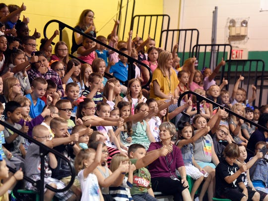 Students give a thumbs-up in the gymnasium during the