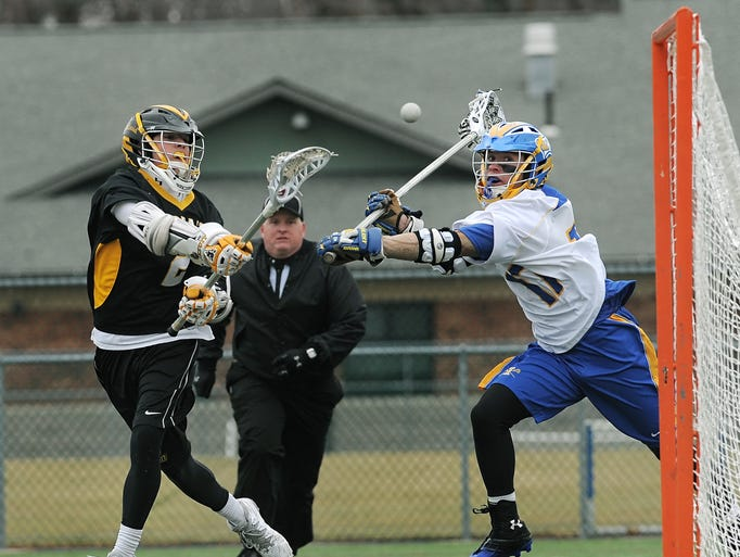 McQuaid's Jake Gleason, right, scores an empty net goal while defended by Irondequoit's Dabiel Harris during a game played at Irondequoit High School on April 5, 2014.  McQuaid beat Irondequoit 9-7.