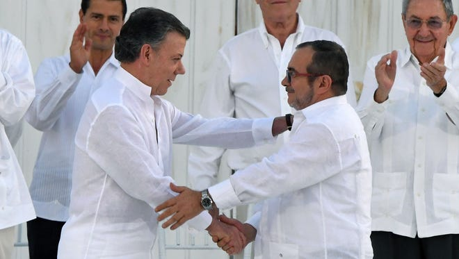 "Colombian President Juan Manuel Santos, left, and the head of the FARC guerrilla group, Rodrigo Londono Echeverri, also known as ""Timoshenko,"" shake hands during the signing of a historic peace agreement in Cartagena, Colombia, on Sept. 26, 2016."