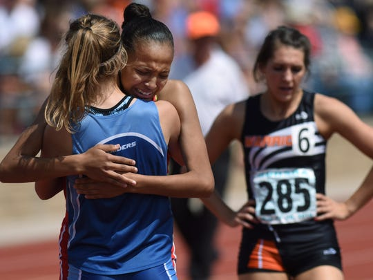 Lincoln's Jasmyne Cooper hugs opponent Rapid City Stevens' Kendra Dykstra after winning the Gilr's 800-meter run during the 2016 South Dakota State Track Meet at McEneaney Field on Friday, May 27, 2016.