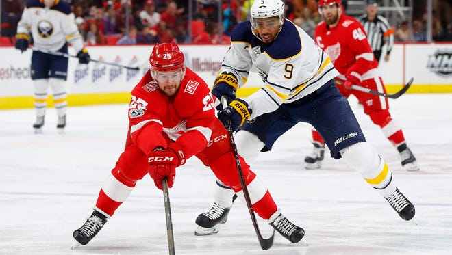 Red Wings defenseman Mike Green (25) and Sabres left wing Evander Kane (9) vie for the puck during the first period on Friday, Nov. 17, 2017, at Little Caesars Arena.