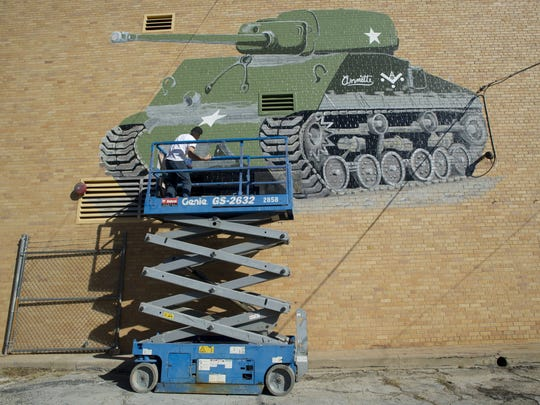 FILE PHOTO: Artist Pedro Rivera refreshes the paint on a tank mural on the wall of the 12th Armored Division Memorial Museum.