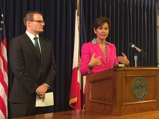 Gov. Kim Reynolds talks with reporters on Monday, June 26, 2017, while Lt. Gov. Adam Gregg stands at her side.