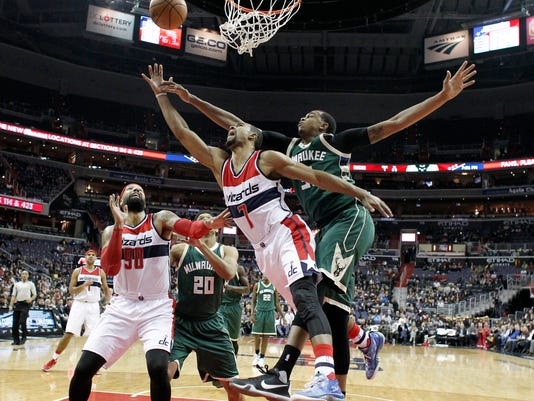 Washington Wizards forward Jared Dudley (1) tries to shoot with Milwaukee Bucks forward John Henson behind him, with Wizards forward Drew Gooden (90) and Bucks guard Rashad Vaughn (20) nearby, during the first half of an NBA basketball game Wednesday, Jan. 13, 2016, in Washington. (AP Photo/Alex Brandon)
