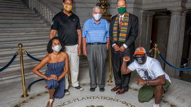 "Ashley Stokes and her father Keith Stokes, both of Newport; Antonio Pires, former House Finance Committee chairman; Sen. Harold Metts, sponsor again of a bill to strip ""Providence Plantations"" from the state's official name; and Brother Gary Dantzler, of Rhode Island's Black Lives Matter organization, from left, pose around the state seal in the floor of the State House Rotunda."