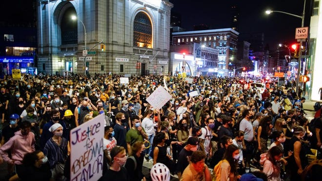 Demonstrators march during a protest following a Kentucky grand jury's decision not to indict any police officers for the killing of Breonna Taylor.
