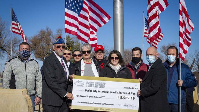 Representatives from Victory Electric presented the Dodge City Veterans Council/Avenue of Flags with a check for $8,069.19. Among them were Mikey Goddard, Victory Electric; Allen Burkhart, president of Avenue of Flags; Roger Jones, Avenue of Flags; Kristin Hughes and Sonya Hughes, daughter and wife of the late Bob Hughes; Charles Sellens, Avenue of Flags; Jerri Whitley, Kyndell Penick, Shane Laws (CEO) and Rob Henry, all of Victory Electric.