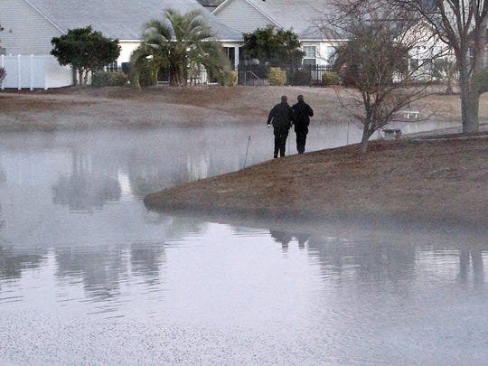 Law enforcement officials search around a retention pond early in the morning in the Hidden Lakes neighborhood of Little River on Friday, Dec. 26, 2014. The body of 4-year-old Jayden Morrison was discovered in this pond.