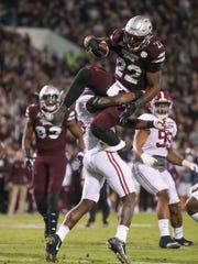 Mississippi State's Aeris Williams (22) hurdles Alabama's