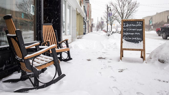Snow piles up in a chalkboard on the empty sidewalk outside of the Exquisite Corpse Coffeehouse in downtown Port Huron. Local schools are closed because of the snow.