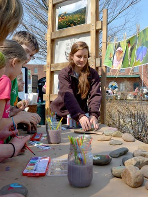 Elise Lintelman of The Natural Garden helps children with painting rocks during last year's Earth Day Staunton.