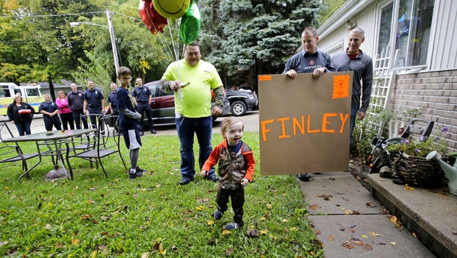 Finley Volkman, who is battling brain cancer, has new friends to help celebrate his third birthday on Sunday, October 2, 2016 in Fox Crossing, Wisconsin. Members of the Fox Crossing Fire Department, Station 40 (rear) along with Clayton Samuelson (with balloons), Scott Wisner and Steve Van Handel and others helped in the celebration.