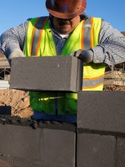 Abel Paredes Jr. lays block at the Chandler Unified