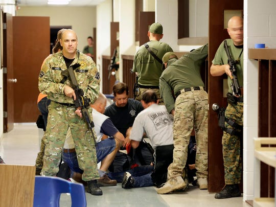 Sheboygan County SWAT team members protect first responders treating a 'victim' during a training session Tuesday, Sept. 8, 2015, at the former Willigen School near Haven.