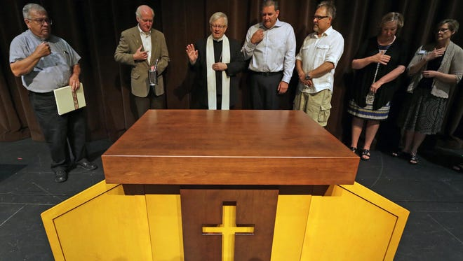 Bishop David Ricken, center, blesses a moveable altar in the Jane Bergstrom Fine Arts Education Center Thursday at St. Mary Central High School in Neenah.