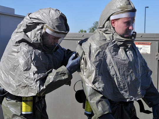 Staff Sgt. Adam Olsen helps Senion Master Sgt. Ian Ball with his decontamination suite during training at the 179th Airlift Wing of the Ohio National Guard.