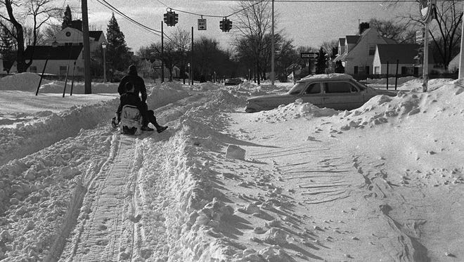 A Lansing resident uses a snowmobile to get around after the record snowfall of January 1967.
