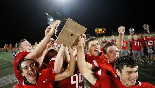 Tappan Zee players hoist the Orange Bowl trophy after