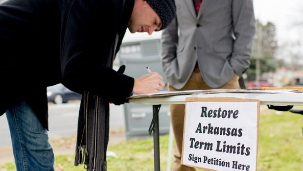 In this Jan. 18 photo, Stuart Rubio, left, signs a